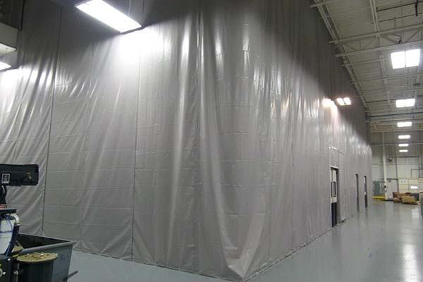 The pvc fabric partition is suspended from the existing roof structure to create a semi-permanent static wall